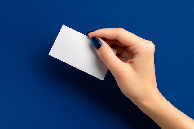 Womans hand holding paper card on blue background. beauty salon mock up greeting card template