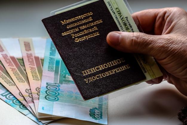 백그라운드에서 러시아 연금 증명서 러시아 루블을 들고 여자 손