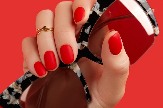 Womans hand holding sunglasses over red background manicure pedicure design trends