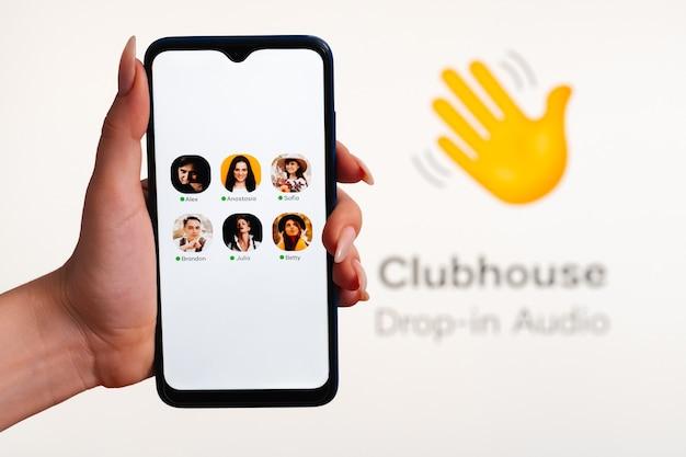 여자의 손은 화면에 클럽 하우스 앱 인터페이스가있는 스마트 폰을 보유하고 있습니다. clubhouse dropin 오디오는 음성으로 활성화되는 소셜 미디어 앱입니다.