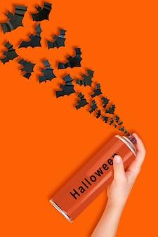 여자의 손은 할로윈 문구가 있는 분무기에서 날아다니는 에어로졸 캔 박쥐를 보유하고 있습니다.