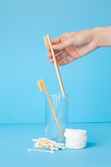 A womans hand holds bamboo toothbrushes on a blue background in a glass
