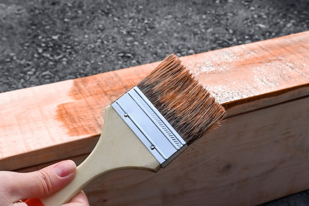 A womans hand holds a paintbrush utdoor painting garden furniture and paintwork