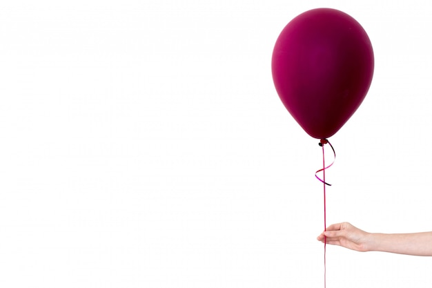 Womans hand holds purple balloon white background