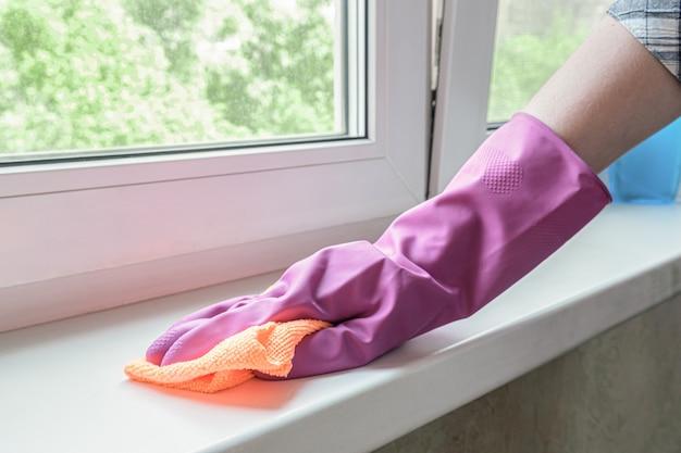 라일락 고무 장갑을 낀 여자의 손은 더러운 플라스틱 창턱을 걸레로 닦는다