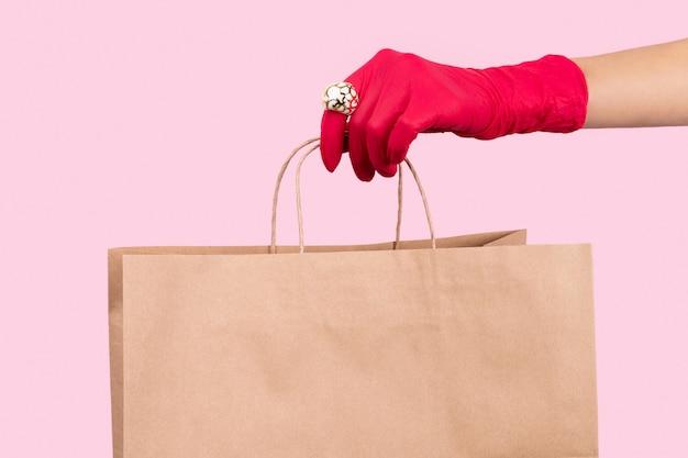 紙袋を保持しているゴム手袋で梨花の手