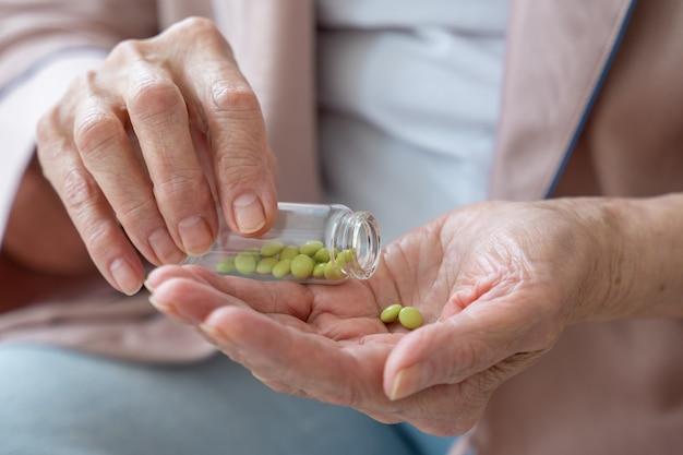 女性の手はクローズアップで薬を持っています年配の女性は彼女の手に錠剤を注いで持っています
