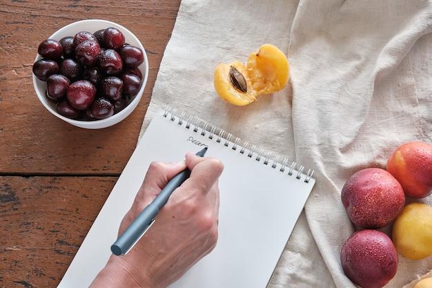 Женская рука пишет ручкой письмо на записной книжке