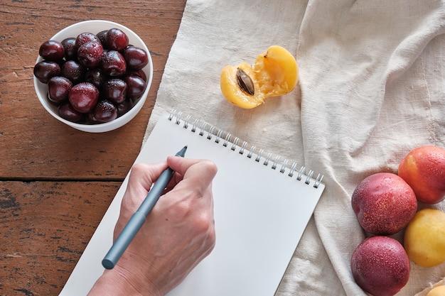 Женская рука пишет ручкой письмо в блокноте