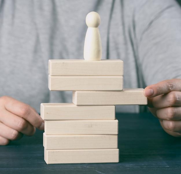 女性の手は、置物が立っている塔から木製のブロックを引き出します