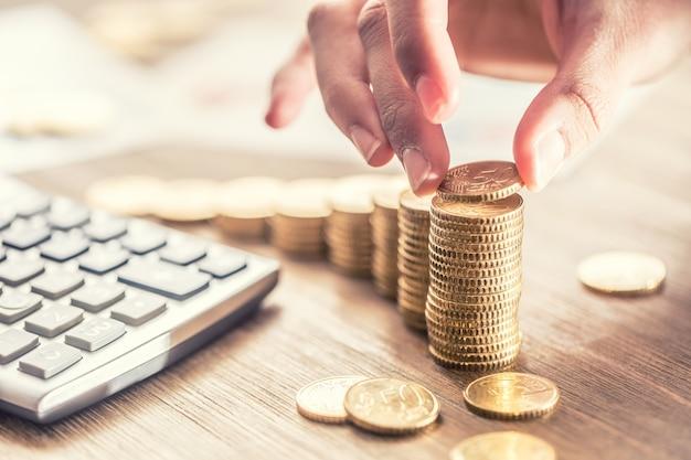 Женская рука положила монеты евро с эффектом роста. натюрморт с cackulator бизнес-плана и евро.