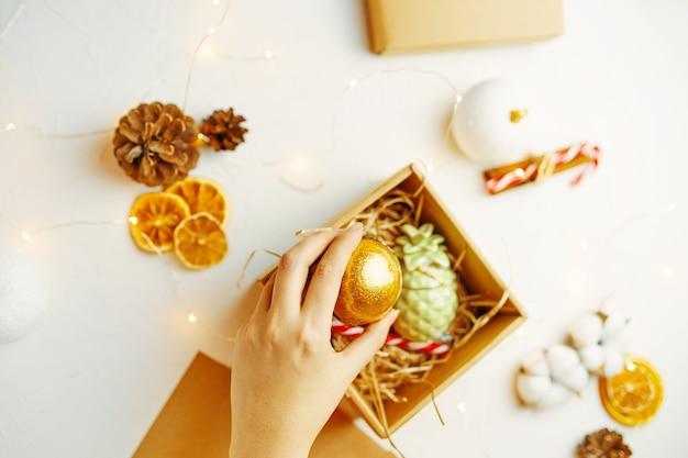 여자의 손은 축제 장식이 있는 흰색 테이블의 선물 상자 평면도에 황금 크리스마스 공을 넣습니다...