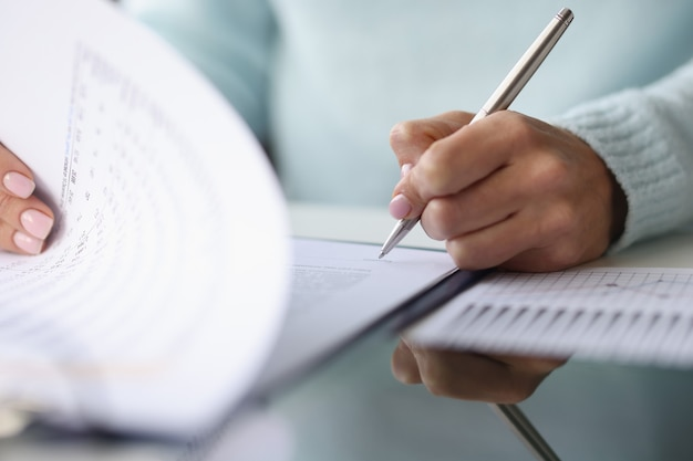 Womans hand puts signature on documents document signing concept