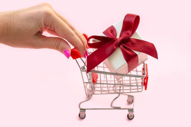 Womans hand rolls shopping trolley with white gift box and red bow on pink background