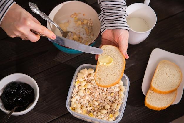 Женщины вручают намазывать сливочным маслом белый хлеб кухонным ножом, готовя утренний завтрак