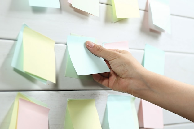 Womans hand sticking notepapers on white wooden board