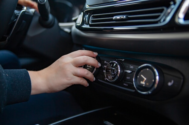 Womans hand switches the air conditioning in the car driver turning on car air conditioning system