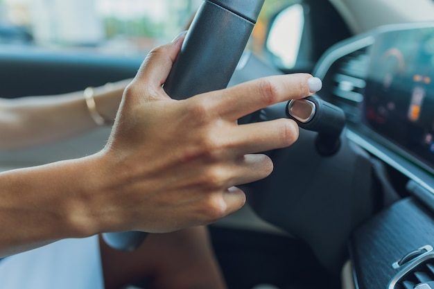 여자의 손은 스티어링 휠에있는 기어 선택기의 로브를 전환합니다. 손은 자동차의 기어 레버를 전환합니다.