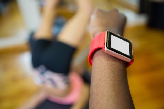 フィットネススタジオでトレーニングしながらスマートな時計を使用して女性の手