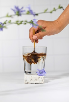 A womans hand will pour granulated chicory powder into a white mug drink chicory