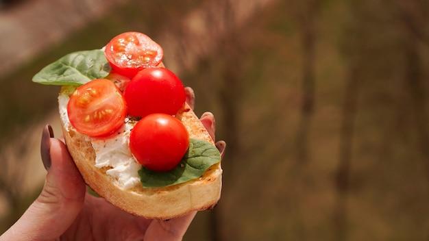 チェリートマトのブルスケッタイタリアワインの前菜と女性の手