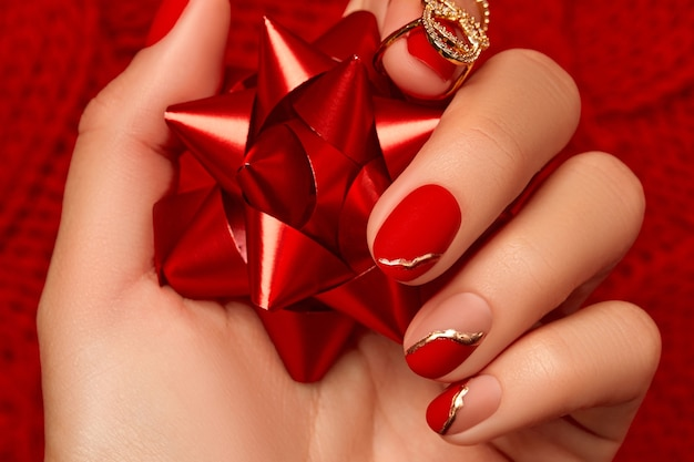 Womans hand with fashionable red manicure close up manicure pedicure beauty salon concept