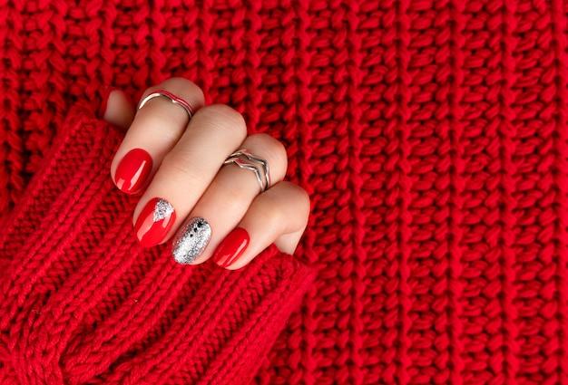 ファッショナブルな赤いマニキュアで女性の手。
