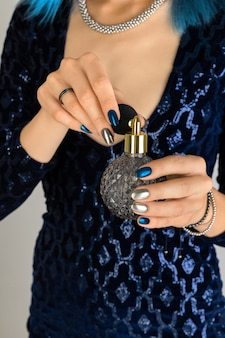 Womans hand with manicure holding bottle of perfume background. party dark night silver nail design.