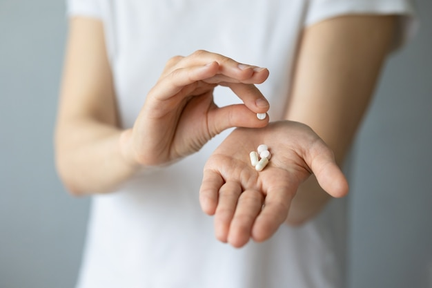 A womans hand with pills in the open palm
