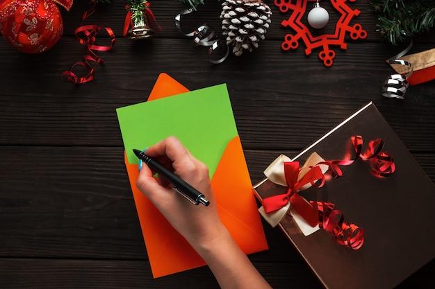 サンタのクリスマスパーティーの手紙の招待状を書く女性の手