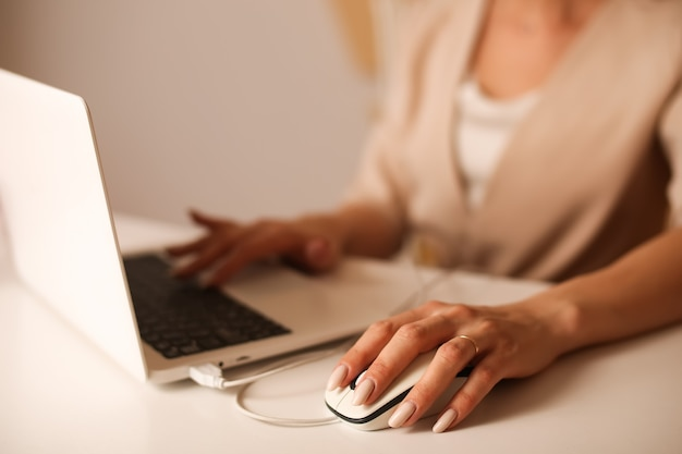 Womans hands are working behind a laptop computer mouse closeup beige suit on a blurred background