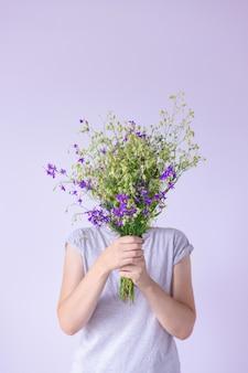 Женские руки держат большой букет диких и луговых цветов на фоне однотонных стен