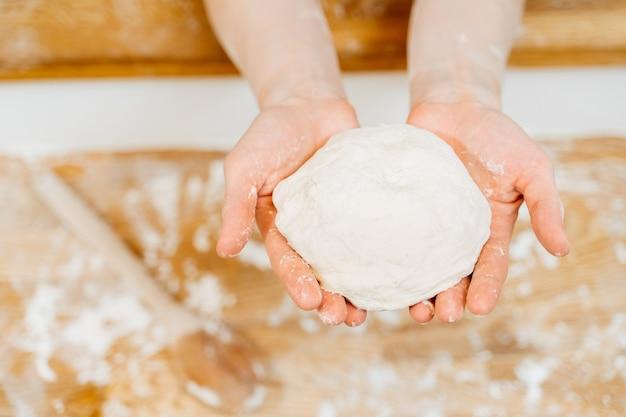 파이와 롤을 만들기위한 원시 반죽을 들고 여자의 손