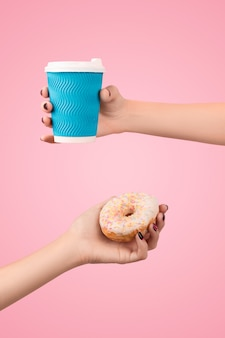 Womans hands holding colorful donut and coffee cup over pink