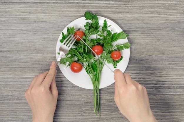 チェリートマトのパセリとプレートの上にフォークとナイフを保持している女性の手
