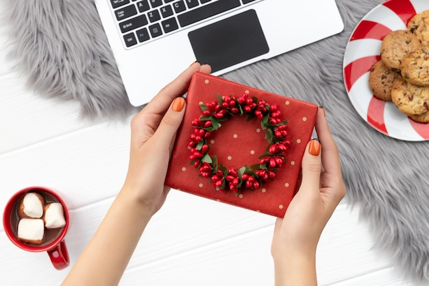 Womans hands holding gift with cocoa and cookies on furry background. christmas online shopping working from home concept.