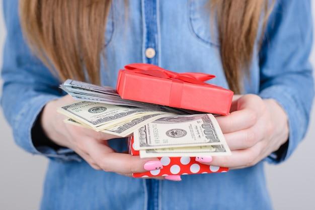 お金でギフトボックスを保持している女性の手