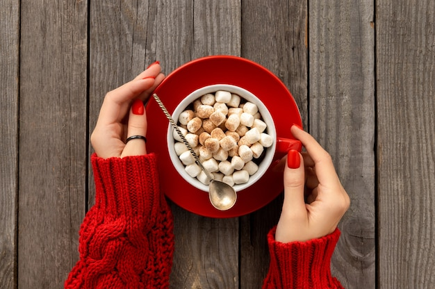 Womans hands holding hot chocolate with marshmallow in red cup on wooden table. christams winter hot drink menu recipe
