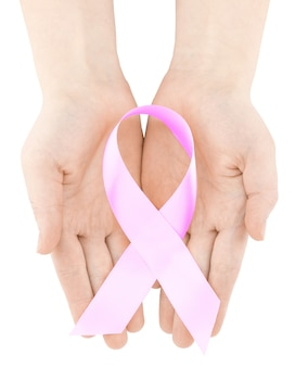 Womans hands holding pink breast cancer awareness ribbon, isolated