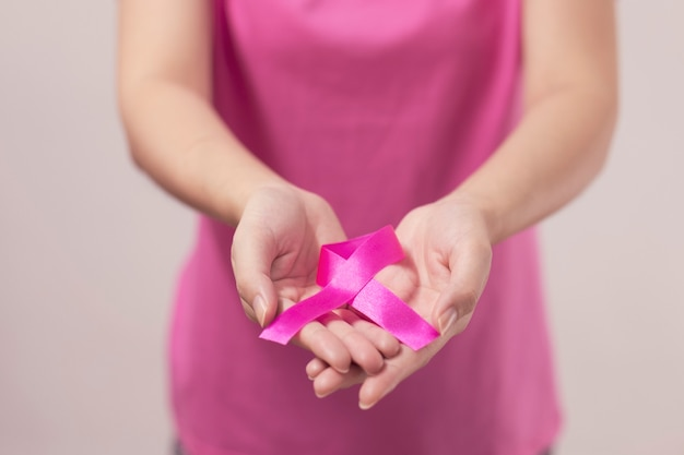 Womans hands holding pink breast cancer ribbon.
