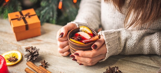 Женские руки в теплом свитере держат чашку ароматного горячего глинтвейна на деревянном столе