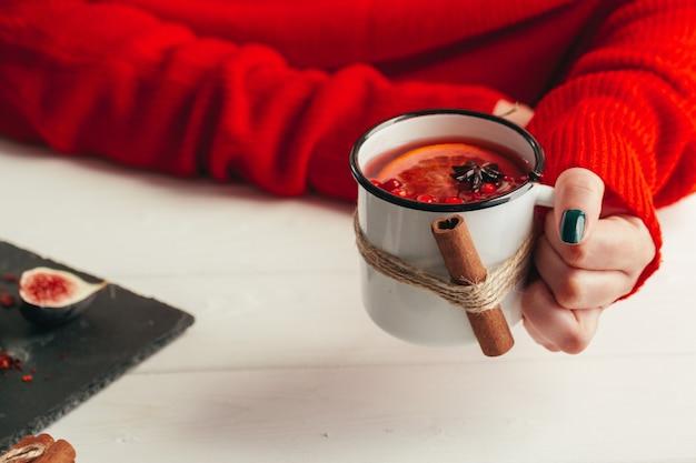 グリューワインのカップを保持している暖かいセーターを手に女性