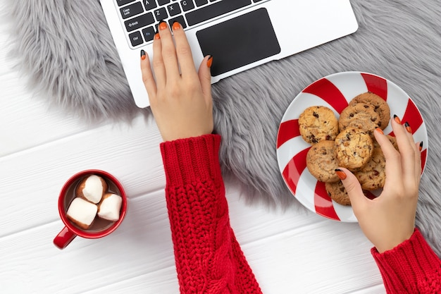 Женские руки, печатающие на клавиатуре с какао и печеньем на пушистом фоне. рождественские покупки в интернете, работая из дома концепции.