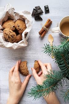 Женские руки с шоколадным печеньем и еловой веткой