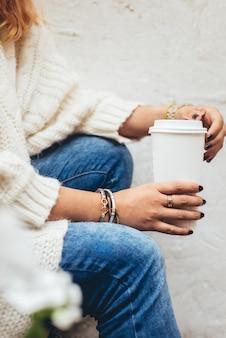 청바지와 크림 스웨터를 입고 일회용 커피 한 잔을 들고 있는 여자의 손