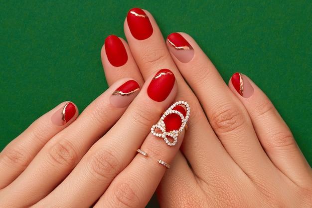 ファッショナブルな赤いマニキュアと女性の手は、クリスマスの新年のネイルデザインをクローズアップ