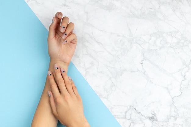 파란색 위에 누드 네일 디자인으로 여자의 손