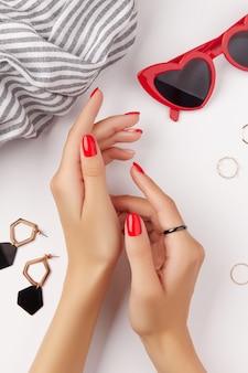 白い背景のマニキュアデザイントレンドに赤いマニキュアとファッションアクセサリーと女性の手