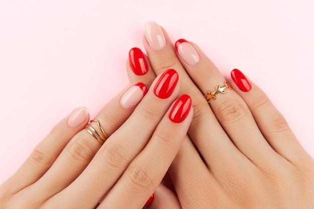 ピンクの表面のマニキュア デザイン トレンドの上に赤いモダンなマニキュアで女性の手