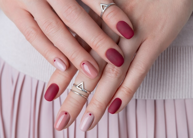 Womans hands with silver jewelry and accessories. girl with minimal pink spring summer manicure design.